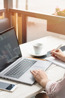 Chiuda sul ritratto di una giovane donna che lavora al computer portatile e che scrive, caffè sul tavolo.