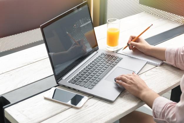 Chiuda sul ritratto di una giovane donna che lavora al computer portatile e che scrive, il succo d'arancia sul tavolo.
