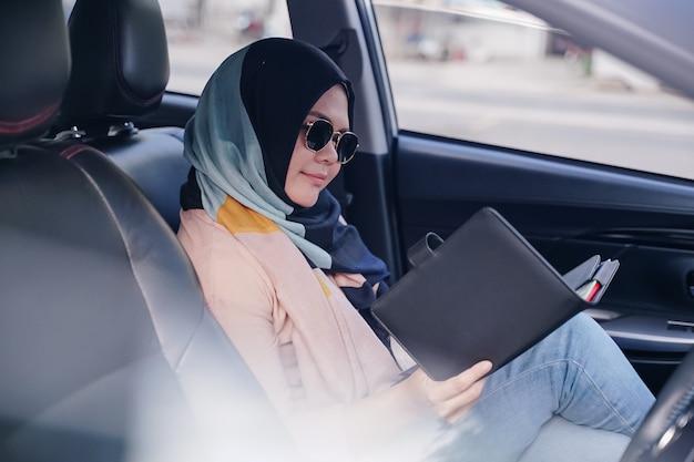 Chiuda sul ritratto di una giovane donna musulmana di affari che legge nel sedile posteriore della macchina.