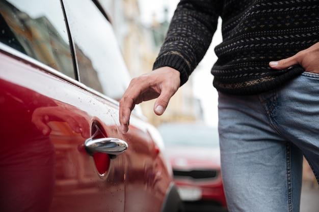 Chiuda sul ritratto di una mano maschio alla maniglia dell'automobile all'aperto