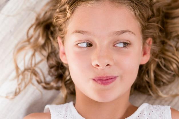 Chiuda sul ritratto di una ragazza giovane e bella del bambino che pensa e che distoglie lo sguardo con l'espressione divertente. occhi verdi, capelli biondi. ambientazione interna. vista dall'alto