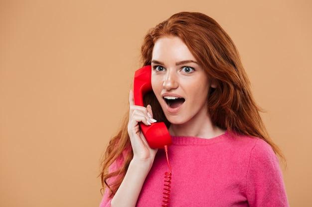 Chiuda sul ritratto di una ragazza sorpresa graziosa della testarossa che parla dal telefono rosso classico