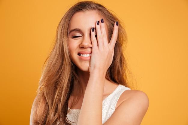 Chiuda sul ritratto di una ragazza sorridente graziosa che copre il suo occhio