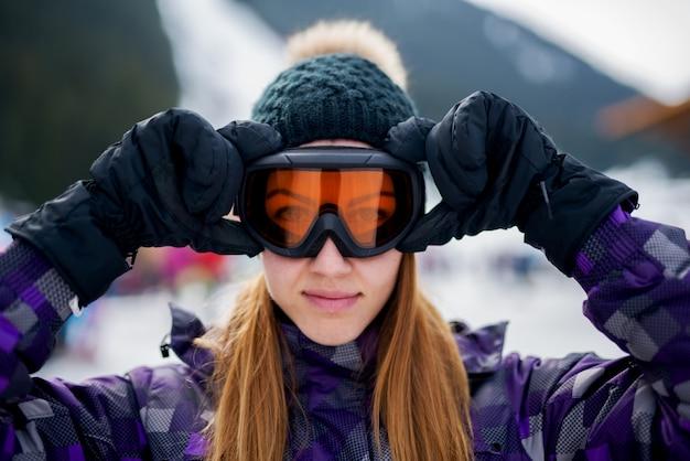 Chiuda sul ritratto di una ragazza sorridente graziosa che indossa i vetri dello sci.