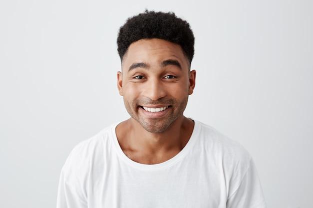 Chiuda sul ritratto isolato del giovane felice allegro con l'acconciatura afro in maglietta bianca casuale che sorride brillantemente, guardando a porte chiuse con espressione eccitata e gioiosa.