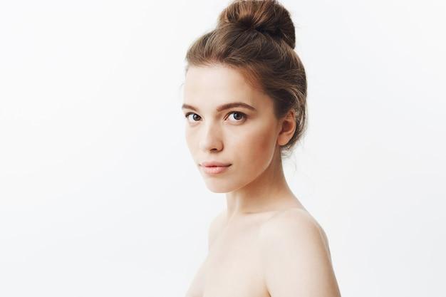 Chiuda sul ritratto isolato di bella giovane donna magra rilassata con capelli scuri lunghi nell'acconciatura del panino, posando mezzo nudo in tre quarti con espressione calma.
