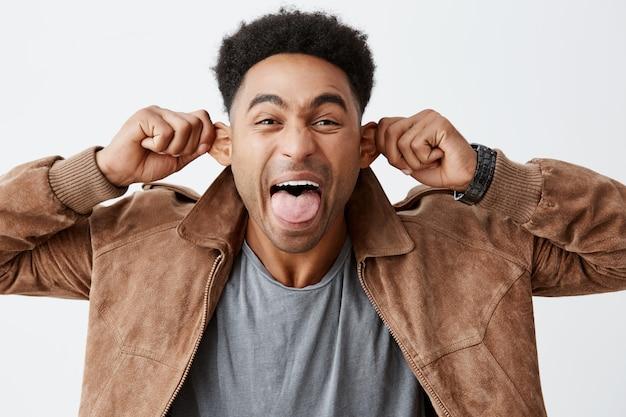 Chiuda sul ritratto isolato di giovane studente universitario dalla pelle nera divertente con le orecchie della tenuta dell'acconciatura afro, mostrando la lingua, facendo l'espressione sciocca del fronte per fare le risate del bambino piccolo.