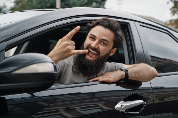 Chiuda sul ritratto laterale dell'uomo felice che conduce l'automobile