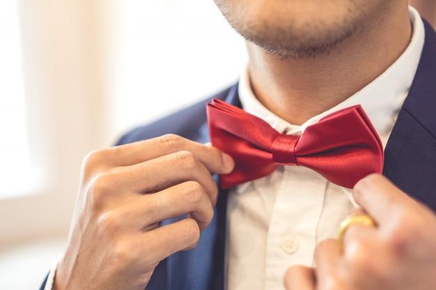 Chiuda sul ritratto un uomo che tocca un farfallino rosso su un vestito. giorno del matrimonio.