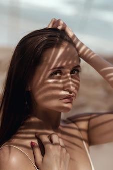 Chiuda sul ritratto una giovane donna sexy con il modello di ombra artistico sul corpo e sul fronte con la spiaggia delle lentiggini.
