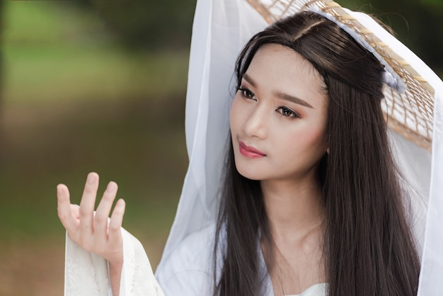 Chiuda sul ritratto vestito bianco dalla bella donna cinese tradizionale