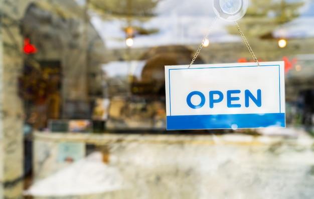 Chiuda sul segno del negozio che mostra lo stato aperto che appende sulla finestra di vetro