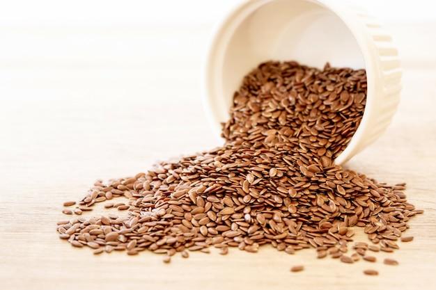 Chiuda sul seme di lino in cucchiaio di legno