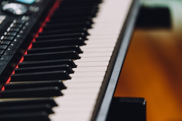 Chiuda sul sintetizzatore elettronico della tastiera musicale con i tasti bianchi e neri.