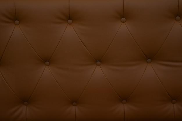 Chiuda sul sofà marrone del leatherette, sul sofà moderno vicino per fondo o sulla struttura.