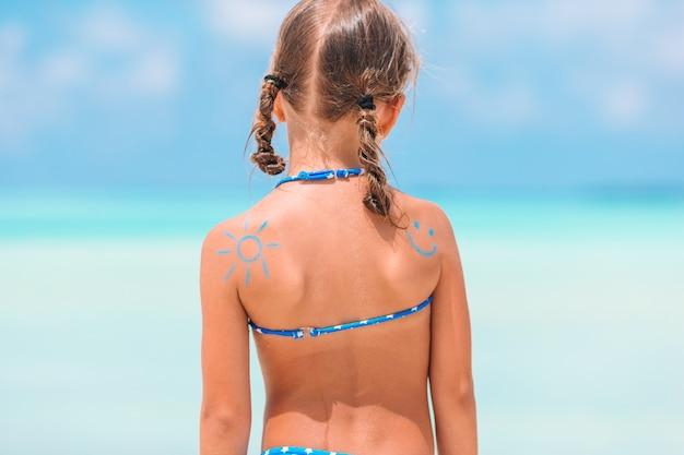 Chiuda sul sole dipinto dalla crema solare sulla spalla del bambino