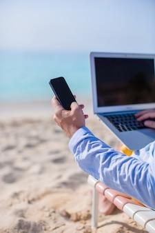 Chiuda sul telefono e sul computer portatile alla spiaggia. lavorando dalla riva del mare