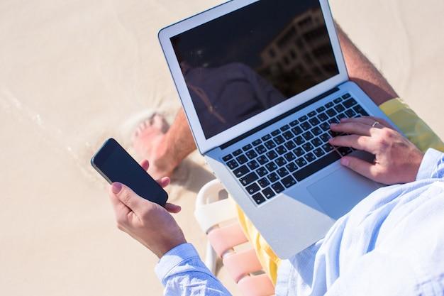Chiuda sul telefono e sul computer portatile alla spiaggia