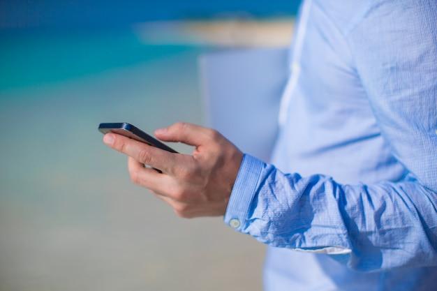 Chiuda sul telefono in mano maschio alla spiaggia tropicale