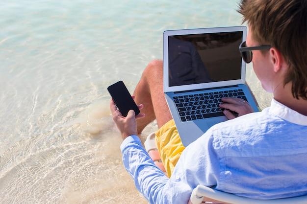 Chiuda sul telefono su fondo del computer alla spiaggia
