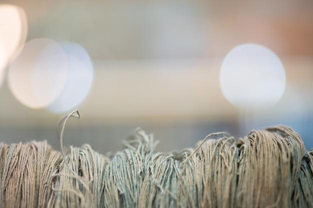 Chiuda sul tessuto di tela del filo sul fondo della luce di bokeh con copyspace