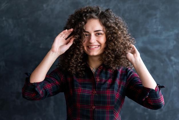Chiuda sul tiro dello studio di una ragazza castana riccia allegra contro la parete grigia, capelli commoventi - l'immagine