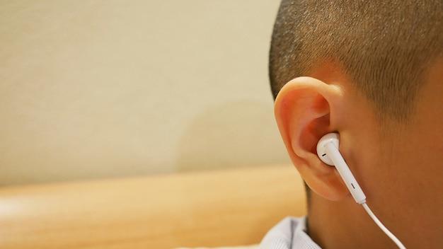 Chiuda sul trasduttore auricolare nel ragazzo dell'orecchio