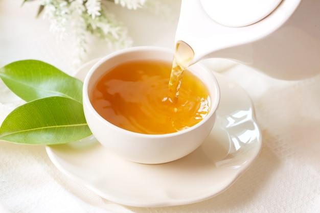 Chiuda sul versamento del tè nero caldo in una tazza di tè bianca