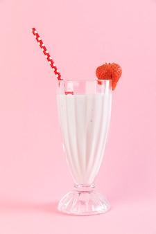 Chiuda sul vetro del frappé della fragola con priorità bassa dentellare
