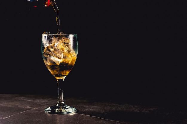 Chiuda sul vetro ghiacciato della cola. bevande analcoliche di acqua frizzante in vetro con ghiaccio