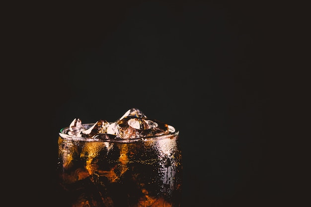 Chiuda sul vetro ghiacciato della cola. bibite di acqua frizzante in vetro con ghiaccio su sfondo scuro