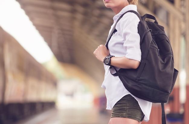 Chiuda sul viaggiatore asiatico dello zaino della donna. donna in piedi alla stazione ferroviaria