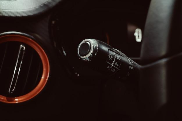 Chiuda sul volante dell'automobile con i bottoni di controllo dei tergicristalli