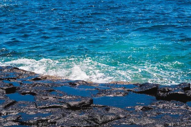 Chiuda sull'acqua ondulata cristallina alla spiaggia
