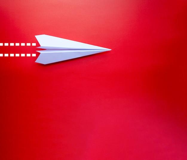 Chiuda sull'aeroplano di carta con priorità bassa isolata