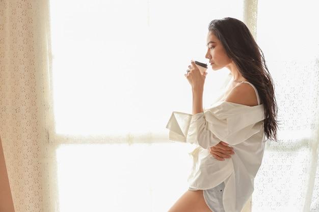 Chiuda sull'artista asiatico della donna in camicia bianca che beve il caffè e si rilassa mentre disegna l'immagine con la matita (concetto di stile di vita della donna)