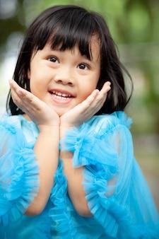 Chiuda sull'emozione sorridente a trentadue denti di felicità del fronte dei bambini asiatici della ragazza del fronte che guarda alla macchina fotografica