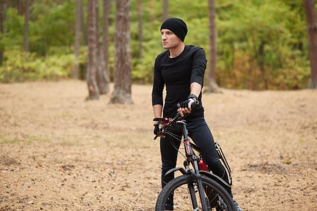 Chiuda sull'immagine del giovane che sta vicino alla sua bici sul sentiero forestale, si ferma per riposare, andare in bicicletta nei fine settimana, passare il tempo libero
