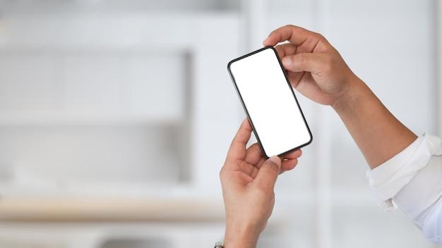 Chiuda sull'immagine dell'uomo d'affari che utilizza il cellulare nell'ufficio