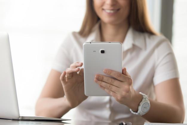Chiuda sull'immagine della compressa digitale in mani della donna