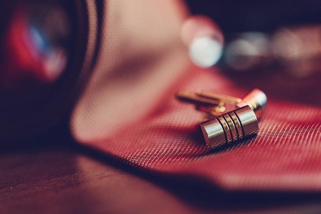 Chiuda sull'immagine della cravatta da uomo e dei gemelli d'argento