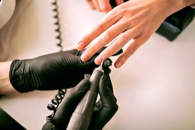 Chiuda sull'immagine della donna che fa manicure hardware, industria dei servizi per unghie, dettagli del salone di moda, maestro di manicure.