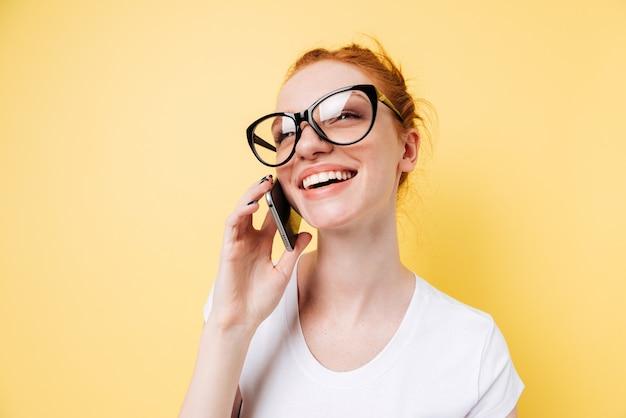 Chiuda sull'immagine della donna felice dello zenzero che parla dallo smartphone
