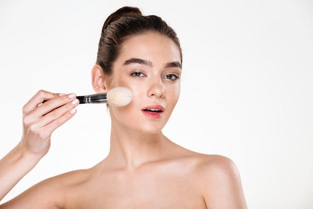 Chiuda sull'immagine della donna mezza nuda tenera con pelle sana che applica la polvere con la spazzola e lo sguardo molli