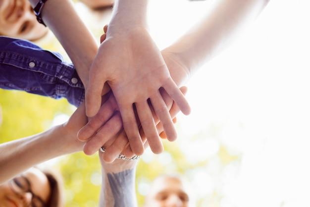 Chiuda sull'immagine delle mani della gente messe insieme. simbolo di lavoro di squadra e unità per raggiungere un determinato obiettivo