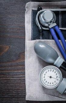 Chiuda sull'immagine dello stetoscopio e del monitor di pressione sanguigna sul concetto di legno d'annata della medicina del fondo