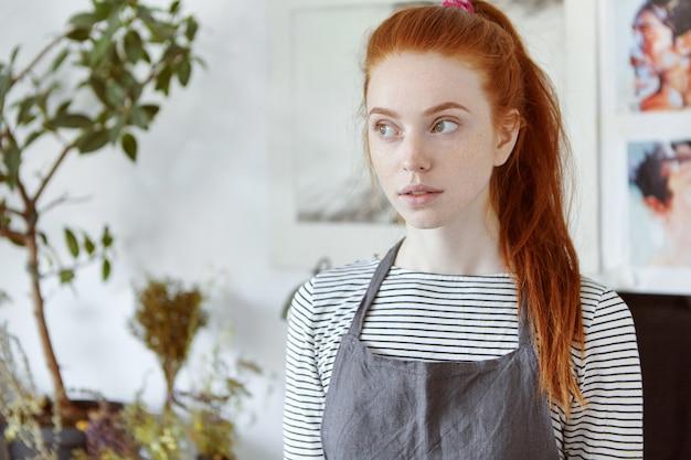 Chiuda sull'immagine di bella studentessa europea dai capelli rossi lentigginosa della scuola di arti nell'officina del college