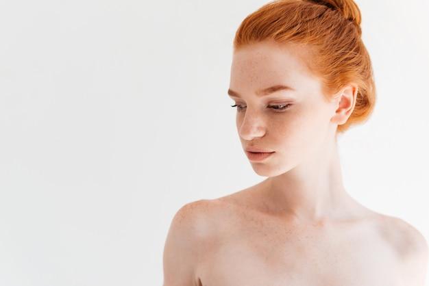 Chiuda sull'immagine di distogliere lo sguardo nudo attraente della donna dello zenzero
