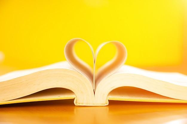 Chiuda sull'immagine di un libro a forma di cuore sul tavolo.