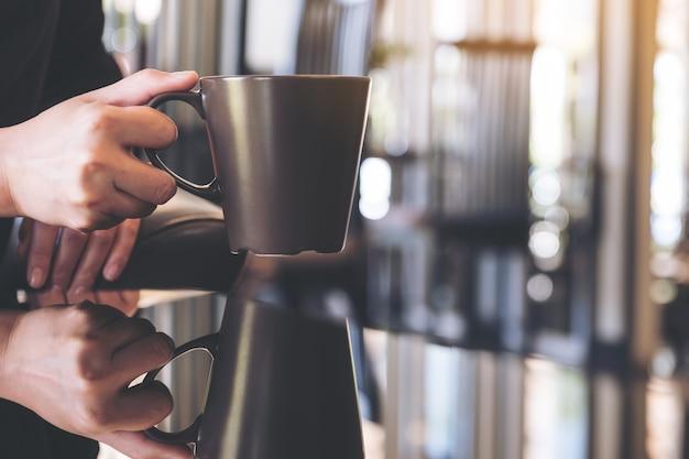 Chiuda sull'immagine di una donna che tiene le tazze da caffè con la riflessione